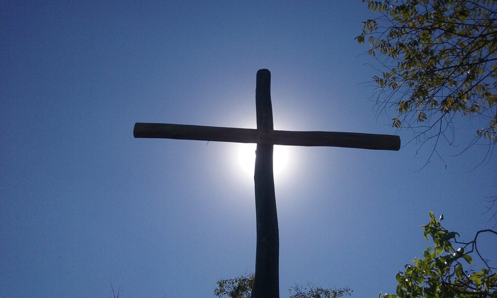 Cruz de madera sobre la luz del sol