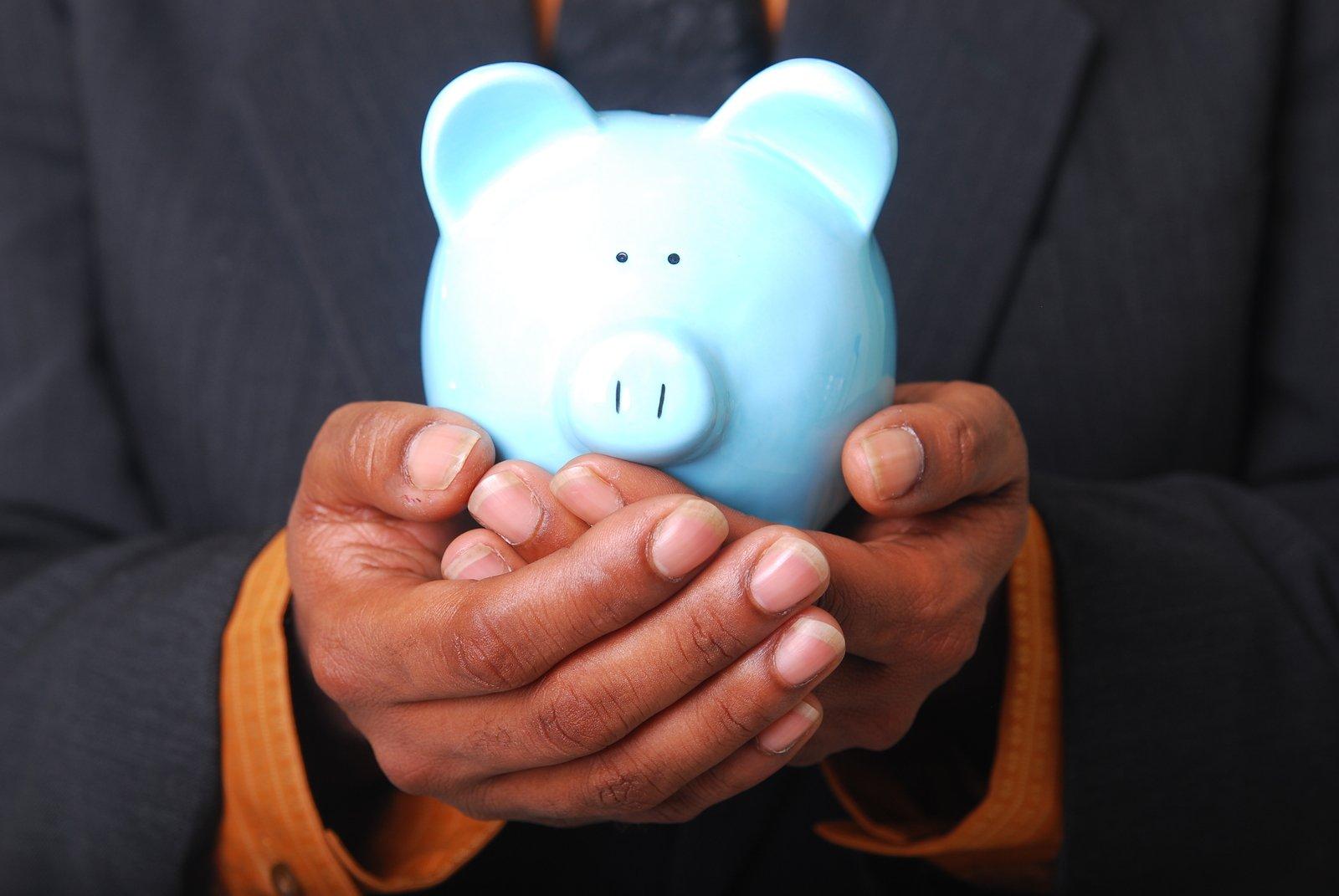 modré prasátko (pokladnička) v dlaních muže v tmavém obleku