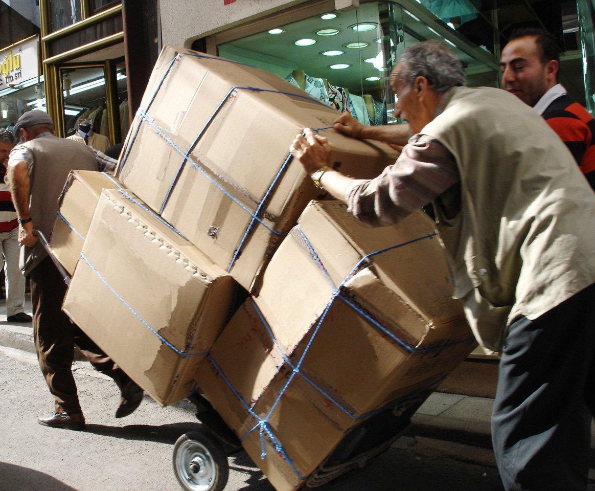 těžká práce (muži tlačící náklad s krabicemi)