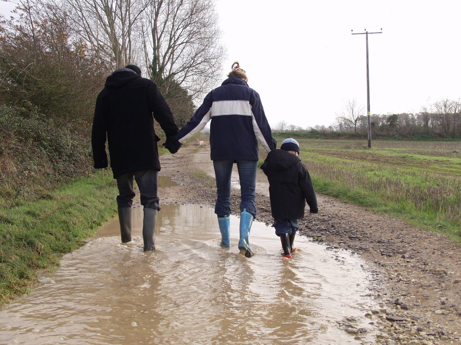 pár s dítětem v gumácích na polní cestě