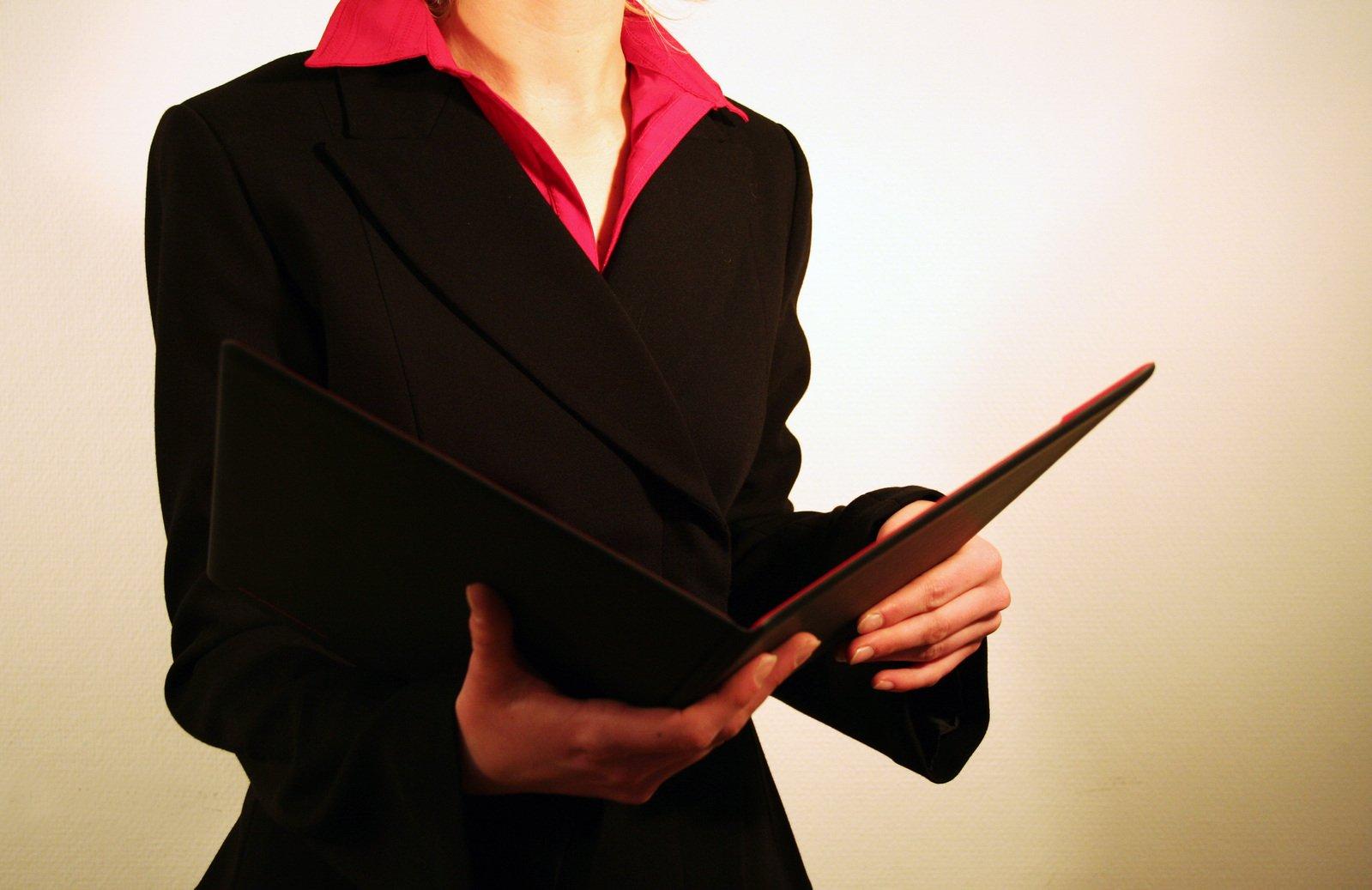 žena v černém saku a červené košili s otevřenou složkou