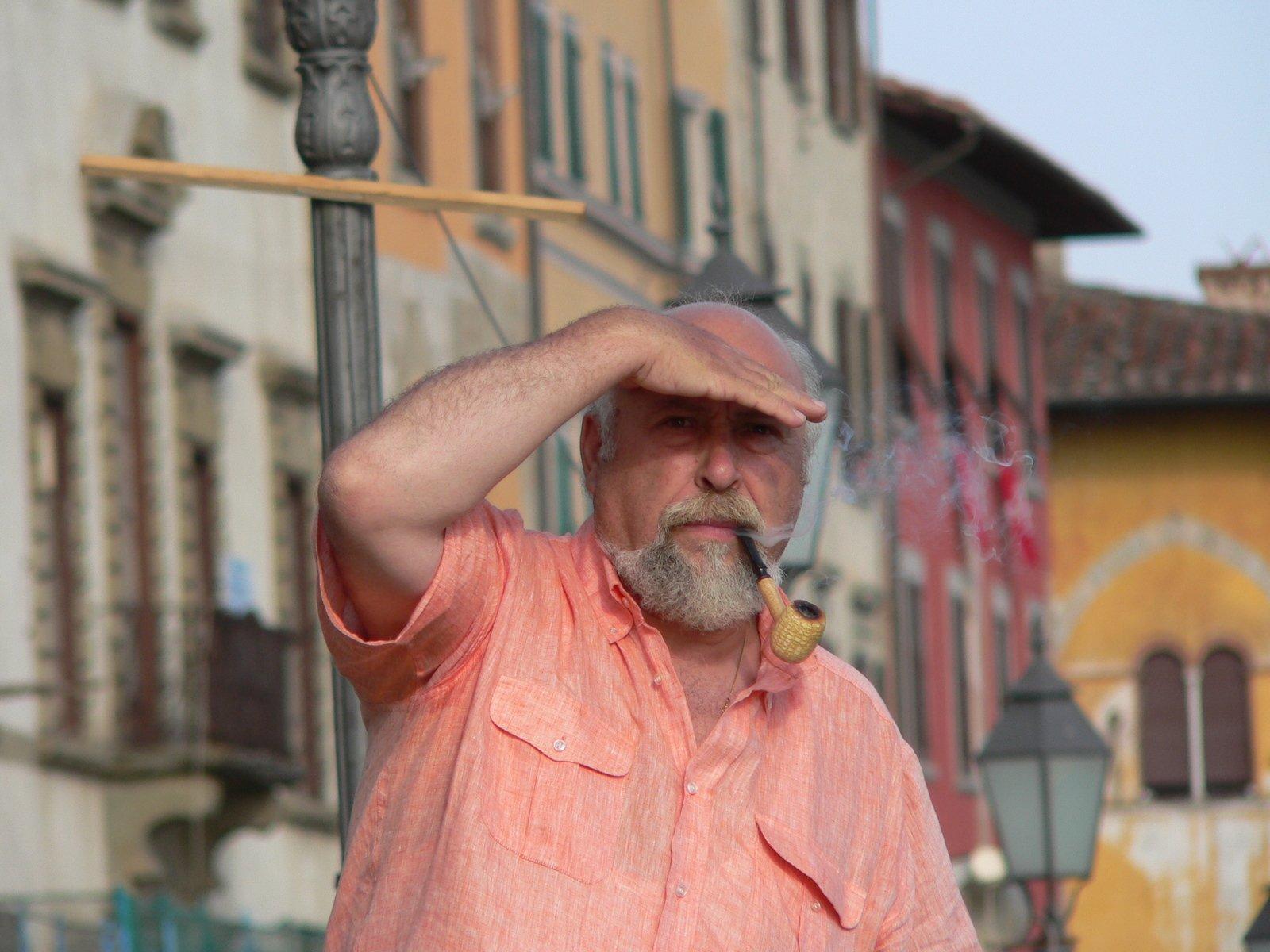 Starší muž s dýmkou, ze které vychází kouř, hledí do dálky. V pozadí jsou barevné staré domy