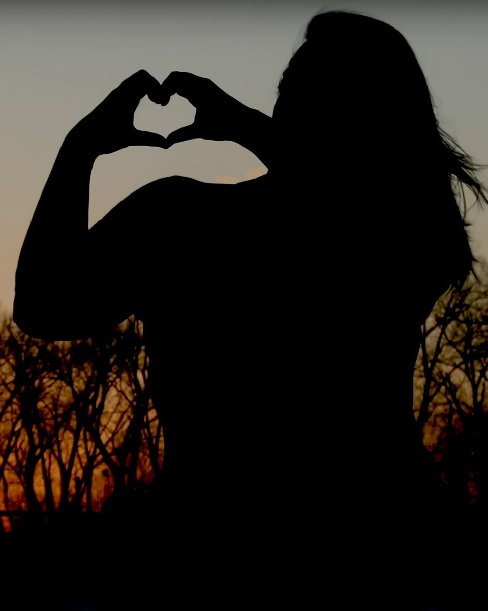 A silhouette of a girl during sunset making a heart symbol with her hands.