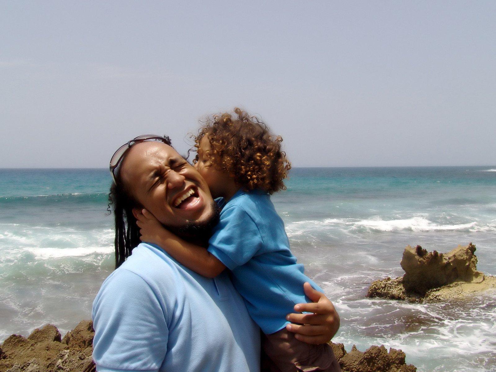 Otec s dítětem v náručí na břehu moře (oba v modrém)
