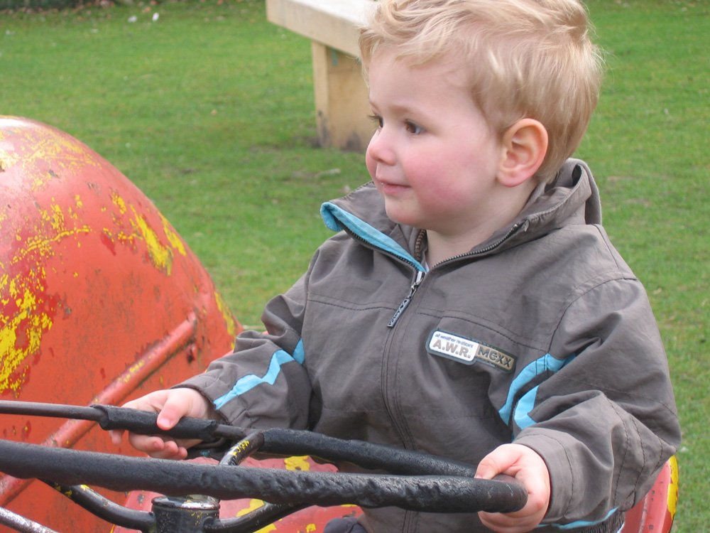 Kid Driving Tractor in Field