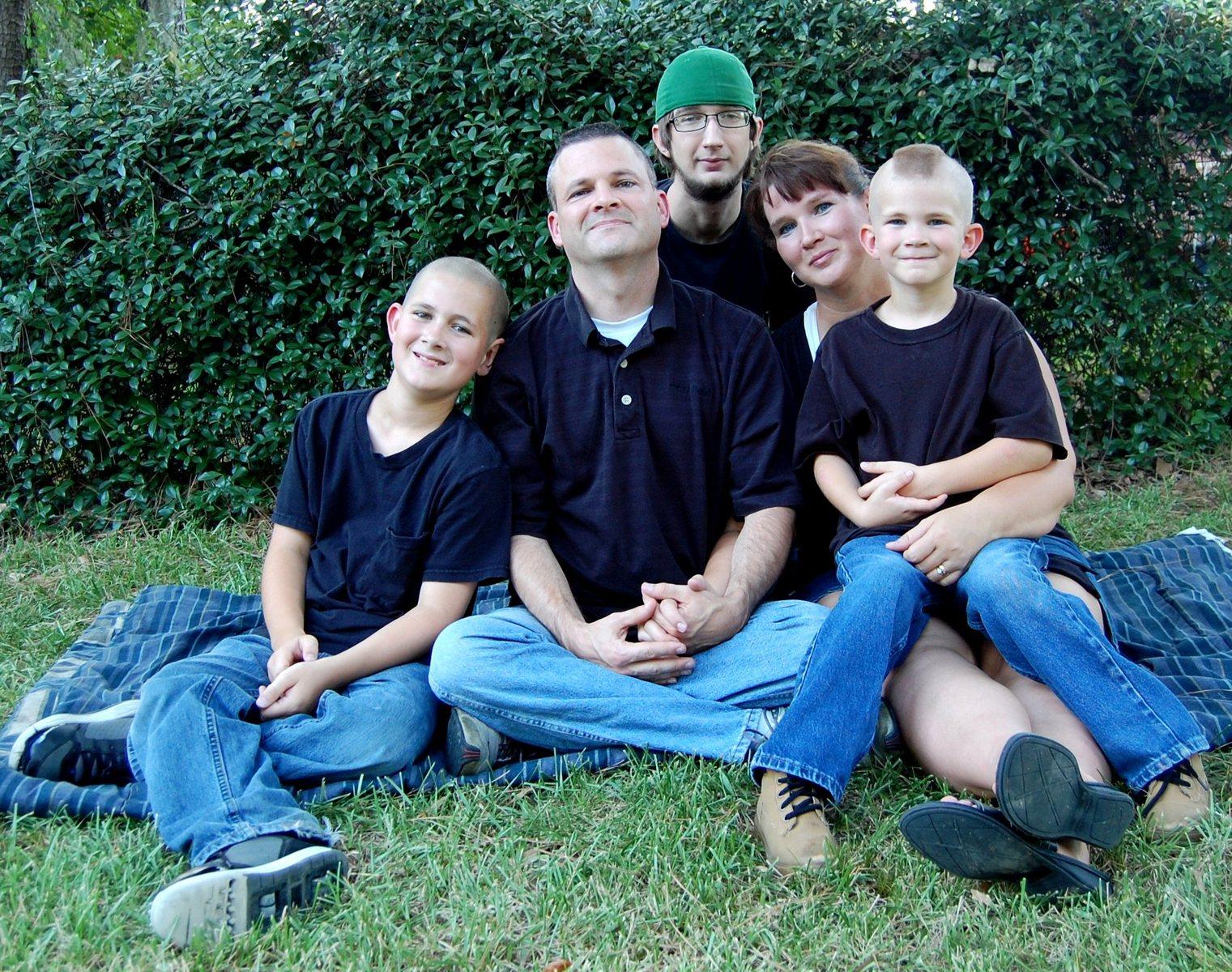 Rodina (rodiče a tři děti v modrém na zelené trávě)