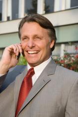 Happy businessman on cellphone.