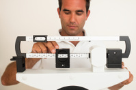 Man adjusting weight scale