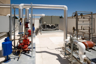 Rooftop HVAC with chiller units and pumps.