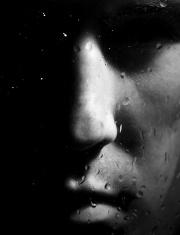 Man looking to the window in dark rainy night
