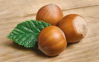 Three whole hazelnuts with leaf on wood background