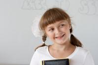 Cute preteen schoolgirl portrait near whiteboard