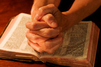 Woman's hands clasped in prayer over Holy Bible