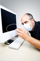 PC user with protective mask is examining a computer mouse