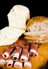 Prosciutto continental food crusty bread wooden chopping board.