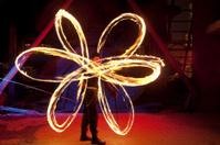 Fire poi dancer showing a flower