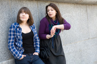 two teen girls talking at stone wall