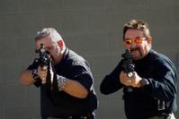 Two mercenaries in black shooting the viewer