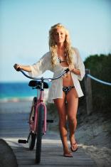 Young woman in bikini walking beach cruiser