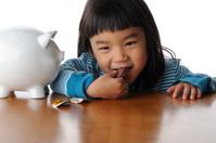Girl Eating Chocolate Coin Next to Piggybank
