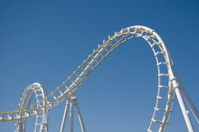 White Rollercoaster Loops Against a Clear Blue Sky