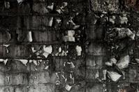 Peeling paint on a black brick wall