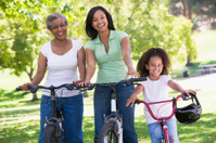 Grandmother with adult daughter and grandchild riding bikes