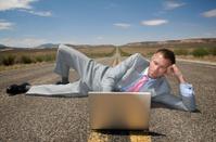 Businessman Lies on Highway w Laptop