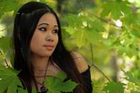 Girl among green leaves