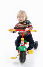 Happy preschooler on a tricycle