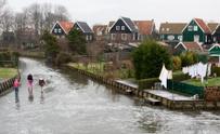 Kids on frozen canal in Dutch residential neighborhood, Winter