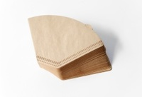Stack unbleached brown coffee filter on white