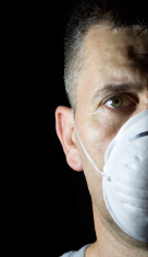 man face with protection mask in dark