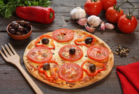 Tomato pizza with some ingredients behind