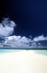 Maldives, southern atolls, surfers on sandbar.