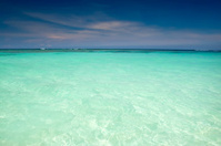 Cyan ocean under blue sky with clouds