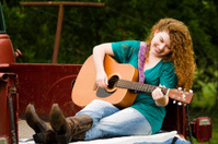Smiling Woman Playing Guitar in Bed of Truck