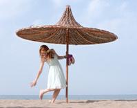 Young Women under Beach Umbrella
