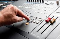 man adjusting a sound board