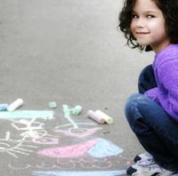Little Girl Sitting Near Chalk Drawings