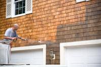 Man Powerwashing a house