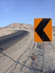 a left sign at uphill roadside