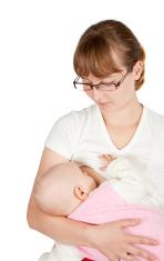 Mum looks at  kid sucking a breast