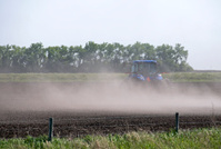 Tractor pulling seeder across field
