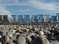 Empty deck chairs on a stoney beach