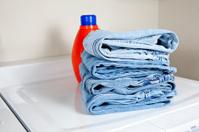 Stack of denim jeans on dryer with detergent bottle XXXL
