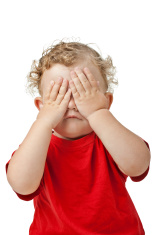 Baby covering eyes with hands playing peekaboo isolated on white
