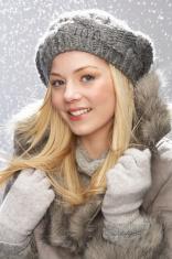 Fashionable Teenage Girl Wearing Cap And Fur Coat In Studio