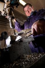 Blacksmith using a drill
