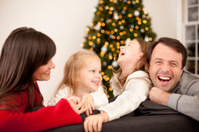 Happy Family Laughing on Couch with Christmas Tree and Lights